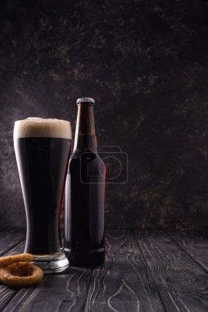 бутылка и стакан пива возле жареных луковых колец на деревянном столе