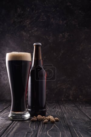 Photo pour Bouteille et verre de bière près de pistaches sur table en bois - image libre de droit