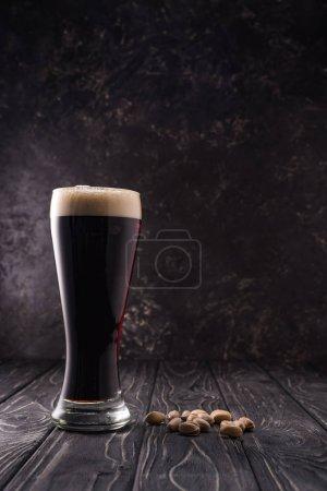 Foto de Vaso de cerveza con espuma cerca de pistachos en la mesa de madera - Imagen libre de derechos
