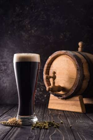 Photo for Glass of beer near wheat spikes and small keg with tap on wooden table - Royalty Free Image