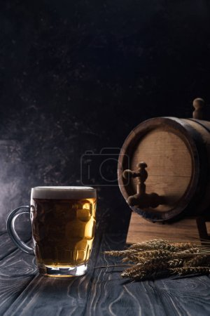 Photo for Mug of light beer near small keg and wheat spikes on wooden table - Royalty Free Image