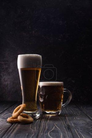 Foto de Vidrio y taza de cerveza fresca ligera cerca de aros de cebolla frita en la mesa de madera - Imagen libre de derechos