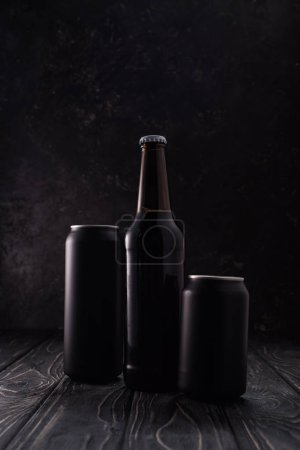 Photo pour Bouteille entre les canettes métalliques noires de bière sur la table en bois - image libre de droit