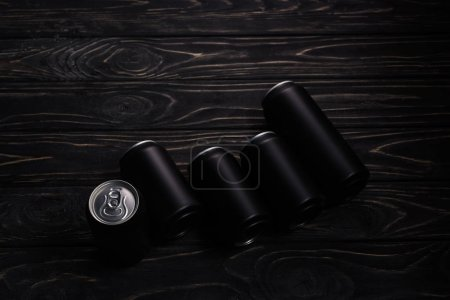 Foto de Latas de aluminio negro de cerveza sobre mesa de madera con espacio de copia - Imagen libre de derechos
