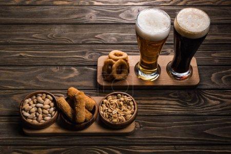 Gläser mit dunklem und hellem Bier mit Schaum in der Nähe von Schüsseln mit Erdnüssen, Pistazien, gebratenem Käse und Zwiebelringen auf Holztisch