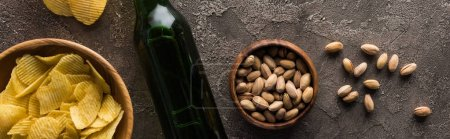 Photo for Panoramic shot of bottle of beer near bowls with pistachios and crisps on brown textured surface - Royalty Free Image