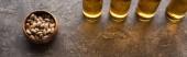 """Постер, картина, фотообои """"панорамный снимок бутылок светлого пива возле фисташек на коричневой текстурной поверхности"""""""
