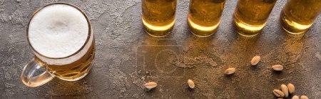 Photo pour Plan panoramique de bouteilles de bière légère près de pistaches éparses sur surface brune texturée - image libre de droit