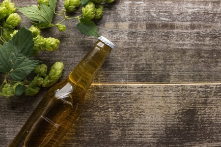 Photo for Top view of beer in bottle with green hop on wooden background - Royalty Free Image