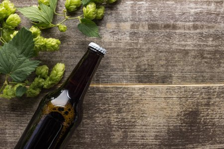 Photo for Top view of beer in brown bottle with green hop on wooden background - Royalty Free Image