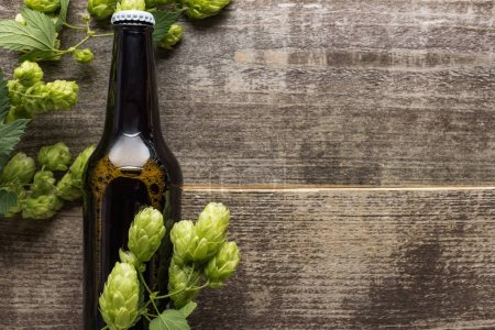 Photo for Top view of beer in brown bottle with green hop on wooden surface - Royalty Free Image