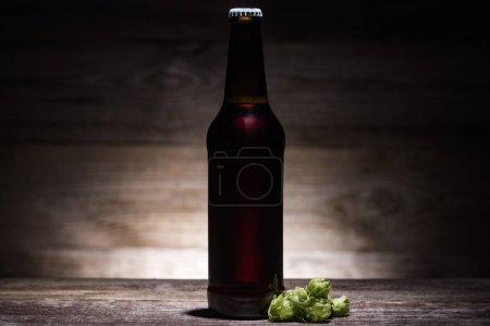 Photo pour Bière dans la bouteille avec le houblon vert sur la table en bois dans l'obscurité avec la lumière arrière - image libre de droit