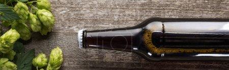 Photo pour Vue du dessus de la bière en bouteille brune avec houblon vert sur fond bois, panoramique - image libre de droit