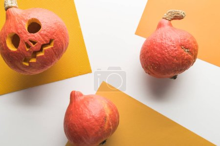 Foto de Vista superior de calabazas de Halloween talladas sobre fondo naranja y blanco - Imagen libre de derechos