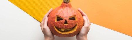 Photo pour Vue recadrée de la femme tenant citrouille Halloween sur fond blanc et orange - image libre de droit