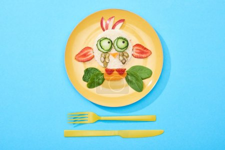 Photo for Top view of plate with fancy face made of food for childrens breakfast near cutlery on blue background - Royalty Free Image