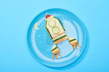 Photo pour Top view of plate with rocket made of food for childrens breakfast on blue background - image libre de droit