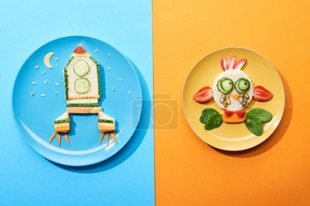 Photo pour Top view of plates with fancy face and rocket made of food for childrens breakfast on blue and orange background - image libre de droit