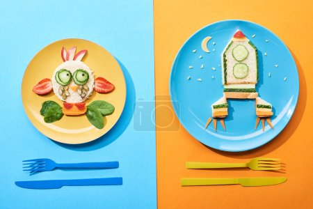 Photo for Top view of plates with fancy face and rocket made of food for childrens breakfast near cutlery on blue and orange background - Royalty Free Image