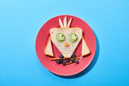 Photo pour Vue du dessus de la plaque avec oiseau de fantaisie faite de nourriture pour le petit déjeuner des enfants sur fond bleu - image libre de droit