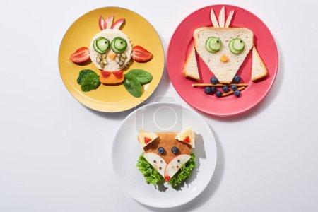 Photo pour Vue supérieure des plats avec la vache de fantaisie, l'oiseau et le renard faitde de la nourriture pour le petit déjeuner d'enfants sur le fond blanc - image libre de droit