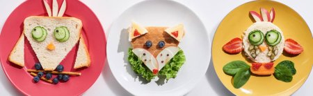 Photo pour Top view of plates with fancy cow, bird and fox made of food for childrens breakfast on white background, panoramic shot - image libre de droit