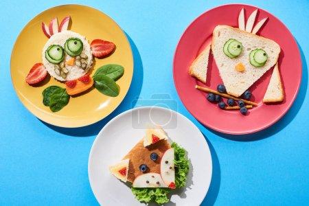 Photo pour Vue de dessus des assiettes avec vache de fantaisie, renard et oiseau fait de nourriture pour le petit déjeuner des enfants sur fond bleu - image libre de droit