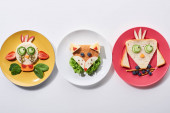 "Постер, картина, фотообои ""top view of plates with fancy cow, bird and fox made of food for childrens breakfast on white background"""