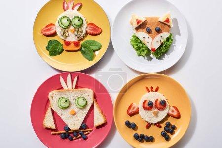 Photo pour Vue supérieure des plats avec des animaux de fantaisie faits de nourriture pour le petit déjeuner d'enfants sur le fond blanc - image libre de droit