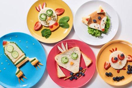 Photo pour Plaques pf de vue supérieure avec des animaux de fantaisie et la fusée faite de nourriture pour le petit déjeuner d'enfants sur le fond blanc - image libre de droit