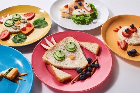 Photo pour Assiettes avec des animaux de fantaisie faits de nourriture pour le petit déjeuner des enfants sur le fond blanc - image libre de droit