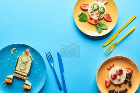 Photo for Top view of plates with fancy animals and rocket made of food for childrens breakfast near cutlery on blue background - Royalty Free Image
