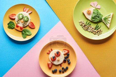 Photo pour Vue de dessus des assiettes avec des animaux de fantaisie faits de nourriture sur fond bleu, jaune et rose - image libre de droit