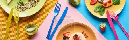 Photo pour Vue de dessus des assiettes avec des animaux de fantaisie faits de nourriture pour le petit déjeuner des enfants sur fond bleu, jaune et rose avec des couverts colorés - image libre de droit
