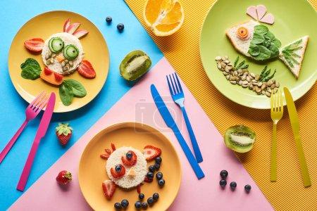 Photo pour Vue supérieure des plats avec des animaux de fantaisie faits de nourriture pour le petit déjeuner d'enfants sur le fond bleu, jaune et rose avec des fourchettes et des couteaux - image libre de droit