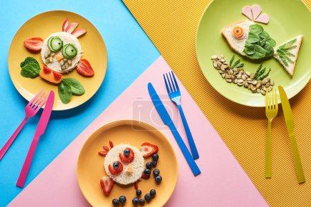 Photo pour Vue supérieure des plats avec des animaux de fantaisie faits de nourriture pour le petit déjeuner d'enfants sur le fond bleu, jaune et rose avec des couverts - image libre de droit