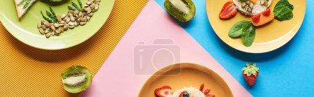 Photo pour Vue supérieure des plats avec des animaux de fantaisie faits de nourriture pour le petit déjeuner d'enfants sur le fond bleu, jaune et rose - image libre de droit