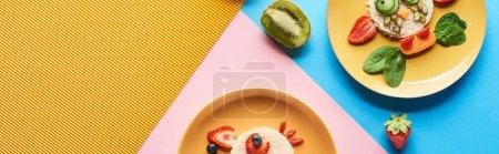 Photo pour Vue de dessus des assiettes avec des animaux de fantaisie faits de nourriture pour le petit déjeuner des enfants sur fond bleu, jaune et rose - image libre de droit