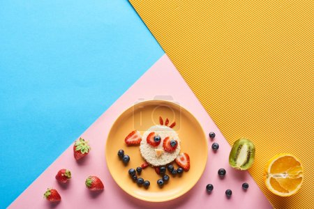 Photo for Top view of plate with fancy animal made of food for childrens breakfast on blue, yellow and pink background - Royalty Free Image