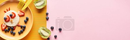 Photo pour Vue supérieure de l'assiette avec l'animal de fantaisie fait de la nourriture pour le petit déjeuner d'enfants près des couverts sur le fond jaune et rose - image libre de droit