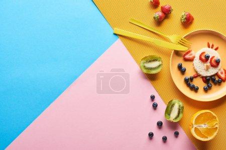 Photo pour Vue supérieure de l'assiette avec l'animal de fantaisie fait de la nourriture pour le petit déjeuner d'enfants près des couverts sur le fond bleu, jaune et rose - image libre de droit
