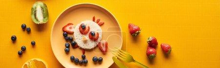 Photo pour Vue supérieure de l'assiette avec l'animal de fantaisie fait de la nourriture sur le fond orange coloré, projectile panoramique - image libre de droit