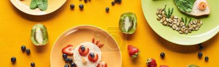 Photo pour Vue supérieure des plats avec des animaux de fantaisie faits de nourriture sur le fond orange coloré, projectile panoramique - image libre de droit