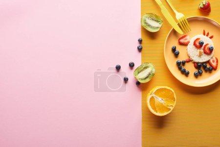 Photo pour Vue supérieure de l'assiette avec l'animal de fantaisie fait de la nourriture pour le petit déjeuner d'enfants près des couverts sur le fond orange et rose - image libre de droit