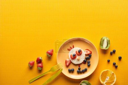 Photo pour Vue supérieure de l'assiette avec l'animal de fantaisie fait de la nourriture près des couverts sur le fond orange coloré - image libre de droit