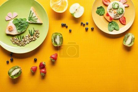 Photo pour Vue de dessus des assiettes avec des poissons de fantaisie et vache faite de nourriture sur fond orange coloré - image libre de droit