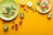 "Постер, картина, фотообои ""top view of plates with fancy fish and cow made of food on colorful orange background"""