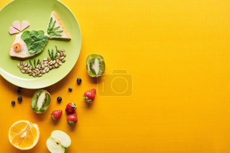 Photo pour Vue de dessus de la plaque avec des poissons de fantaisie faits de nourriture près des fruits sur fond orange coloré - image libre de droit