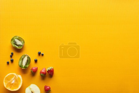 Photo for Top view of strawberry, blueberry, kiwi and orange on colorful orange background - Royalty Free Image