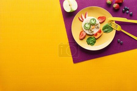 Photo pour Vue supérieure de l'assiette avec la vache de fantaisie faite de nourriture avec des couverts sur le fond pourpre et orange - image libre de droit